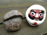 Stone Daruma figure next to a papier mache version